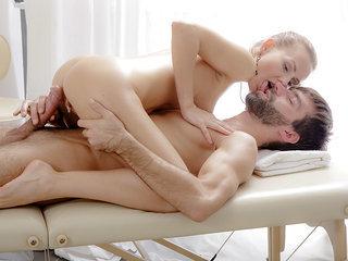 Julie lifts one leg to let masseuse..